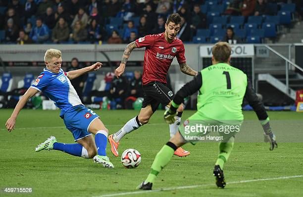 Joselu of Hannover scores his team's second goal past goalkeeper Oliver Baumann of Hoffenheim and Andreas Beck of Hoffenheim during the Bundesliga...