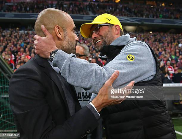 Josep Guardiola head coach of Bayern Muenche greets Juergen Klopp head coach of Dortmund at the start of the DFB Cup semi final match between FC...