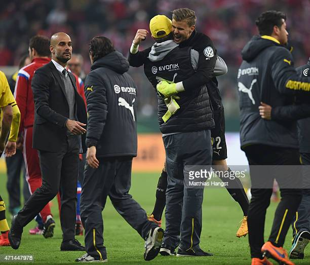 Josep Guardiola, head coach of Bayern Muenche watches as Juergen Klopp head coach of Dortmund celebrates with goal keeper Mitchell Langerak after...