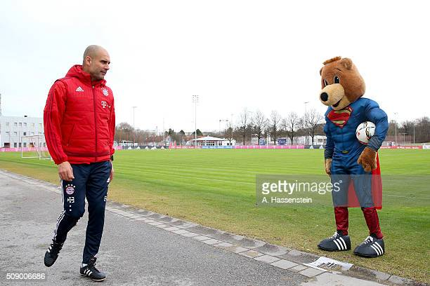 Josep Guardiola head coach of Bayern Muenchen and mascot Bernie dressed as Superman prior to a training session at Bayern Muenchen's training ground...