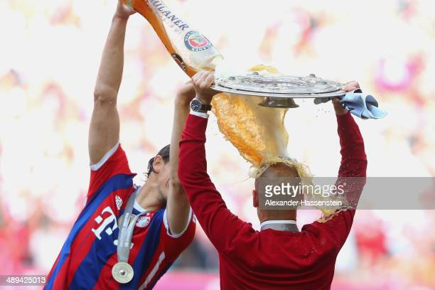 Josep Guardiola head coach of Bayern Muenchen is showered with beer by Daniel Van Buyten as he celebrates with the Bundesliga championship trophy...