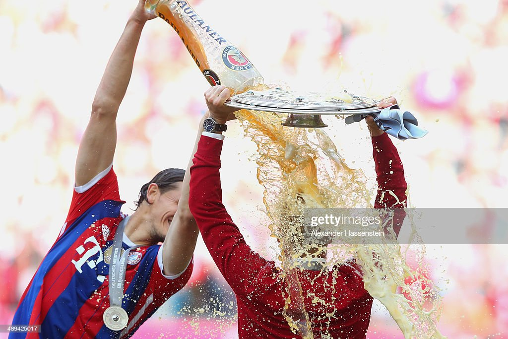 Josep Guardiola head coach of Bayern Muenchen is showered with beer by Daniel Van Buyten as he celebrates with the Bundesliga championship trophy after the Bundesliga match between Bayern Muenchen and VfB Stuttgart at Allianz Arena on May 10, 2014 in Munich, Germany.