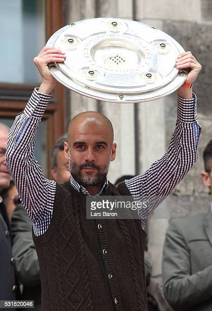Josep Guardiola head coach of Bayern Muenchen lifts the Meisterschale as Bayern Muenchen celebrate winning the Bundesliga at Marienplatz on May 15...