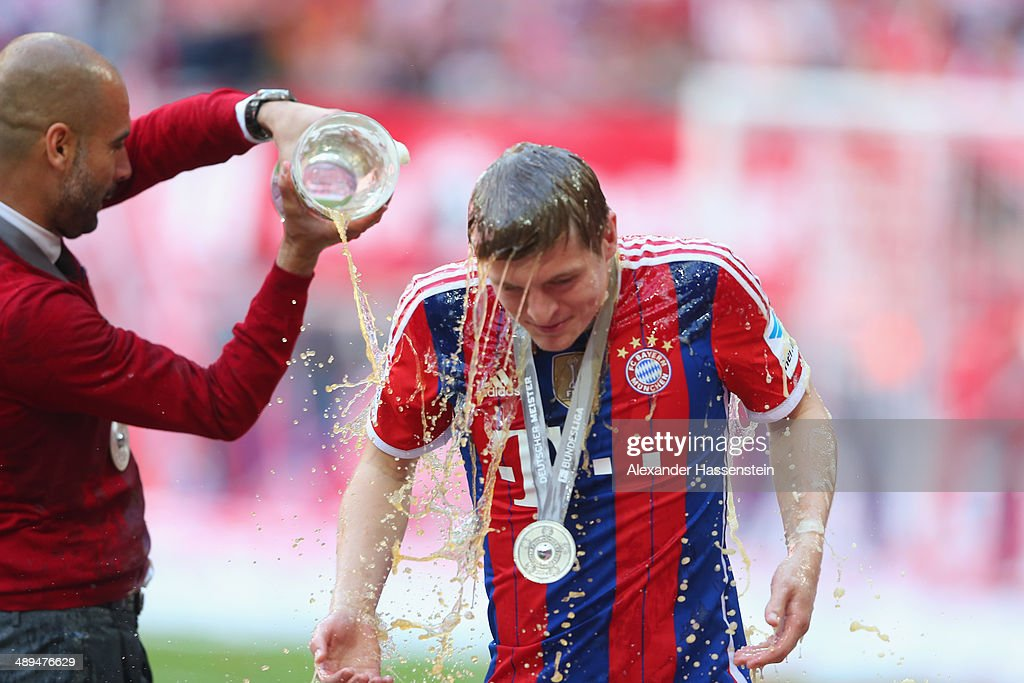 Josep Guardiola head coach of Bayern Muenchen poors beer over his player Toni Kroos as he celebrates with the Bundesliga championship trophy after the Bundesliga match between Bayern Muenchen and VfB Stuttgart at Allianz Arena on May 10, 2014 in Munich, Germany.