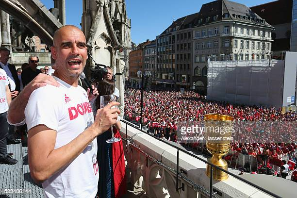 Josep Guardiola head coach of Bayern Muenchen reacts as KarlHeinz Rummenigge CEO of Bayern Muenchen speaks to the crowd as they celebrate the winning...
