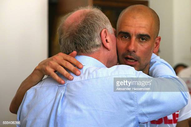 Josep Guardiola head coach of Bayern Muenchen talks to Uli Hoeness after the celebration of winning the DFB German Cup title on the town hall balcony...