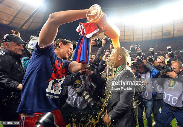 Josep Guardiola head coach of FC Bayern Muenchen gets showered in beer by Daniel van Buyten after winning the DFB Pokal between FC Bayern Muenchen...