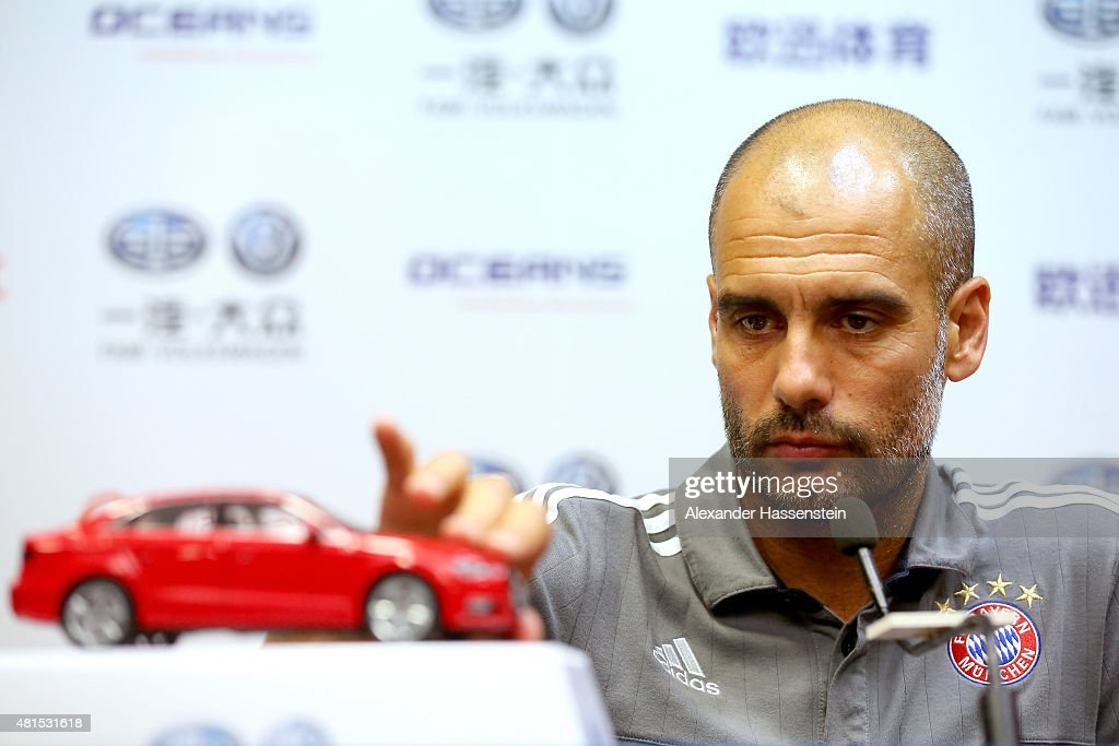 Josep Guardiola, head coach of FC Bayern Muenchen plays with a model car during a press conference at Tianhe Stadium on day 6 of the FC Bayern Audi China Summer Pre-Season Tour on July 22, 2015 in Guangzhou, China.