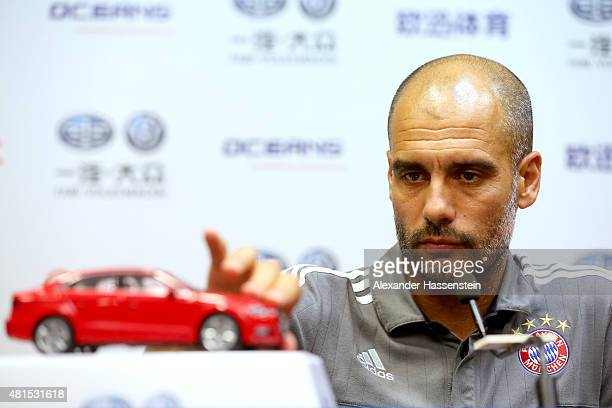 Josep Guardiola, head coach of FC Bayern Muenchen plays with a model car during a press conference at Tianhe Stadium on day 6 of the FC Bayern Audi...