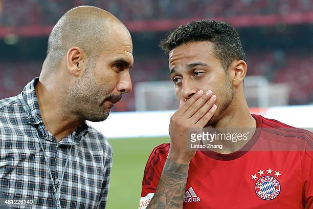 Josep Guardiola, head coach of FC Bayern Muenchen talks to his player Thiago during the international friendly match between FC Bayern Muenchen and...