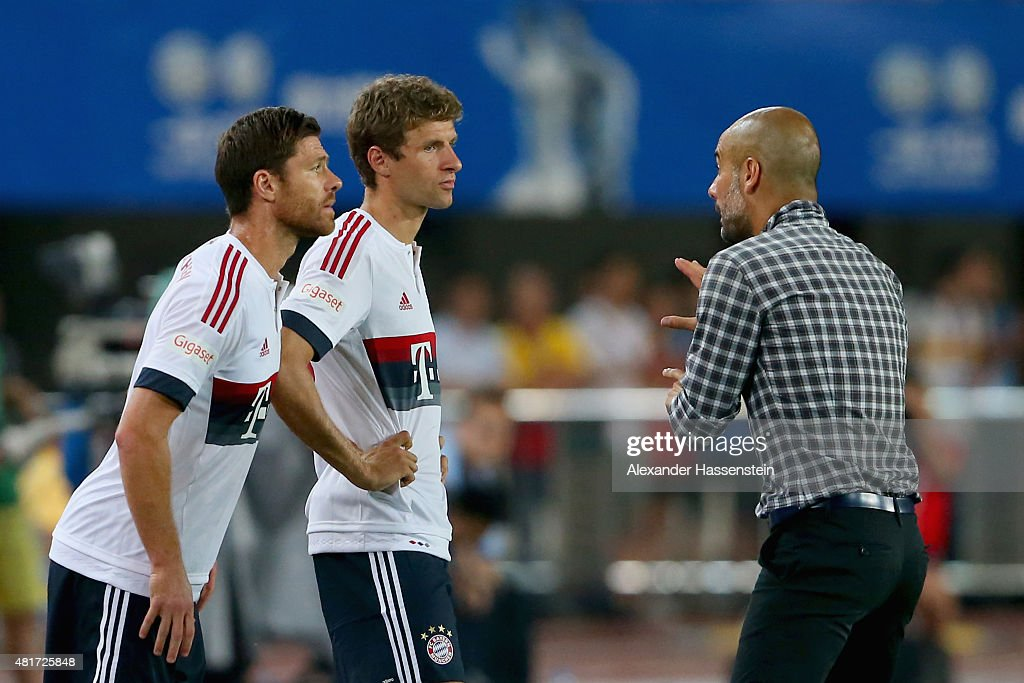 Josep Guardiola, head coach of Muenchen gives instructions to his playres Xabi Alonso (L) and Thomas Mueller during the international friendly match between FC Guangzhou Evergrande Taobao FC and FC Bayern Muenchen of the Volkswagen Cup Guangzhou at Tianhe Stadium on July 23, 2015 in Guangzhou, China.