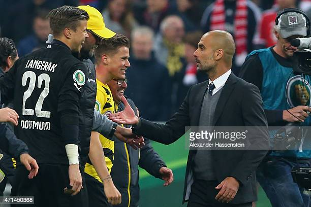 Josep Guardiola head coach of Muenchen shake hands with Juergen Klopp head coach of Dortmund after the DFB Cup Semi Final match between FC Bayern...