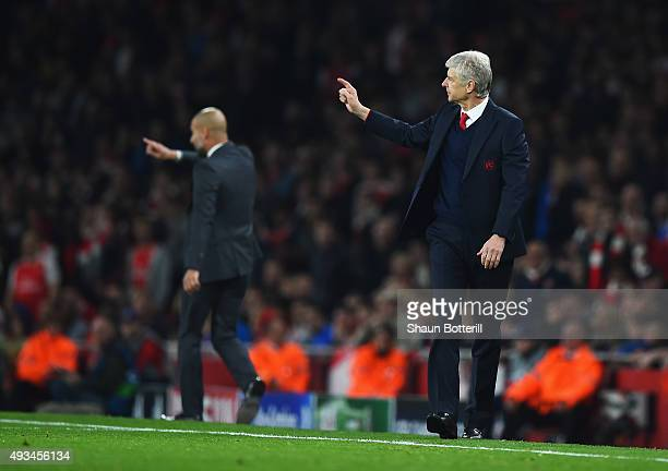 Josep Guardiola manager of Bayern Munich and Arsene Wenger manager of Arsenal signal from the touchline during the UEFA Champions League Group F...