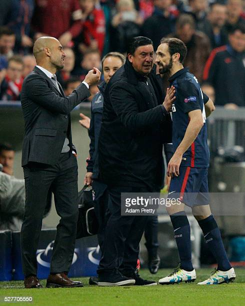 Josep Guardiola manager of Bayern Munich argues with Juanfran of Atletico Madrid as German Burgos assistant coach of Atletico Madrid intervenes...
