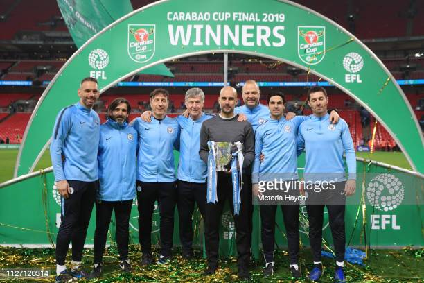 Josep Guardiola Manager of Manchester City and coaching staff celebrate victory with the trophy after the Carabao Cup Final between Chelsea and...