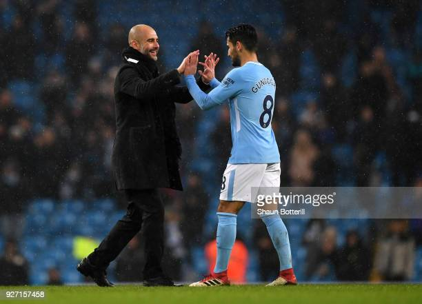 Josep Guardiola Manager of Manchester City and Ilkay Gundogan celebrate following the Premier League match between Manchester City and Chelsea at...