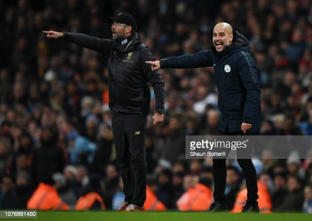 Josep Guardiola Manager of Manchester City and Jurgen Klopp Manager of Liverpool give their team instructions during the Premier League match between...