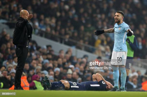 Josep Guardiola Manager of Manchester City and Nicolas Otamendi of Manchester City react as Harry Kane of Tottenham Hotspur goes down holding his...
