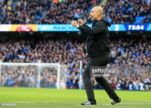 Josep Guardiola Manager of Manchester City celebrates his sides third goal during the Premier League match between Manchester City and Arsenal at...