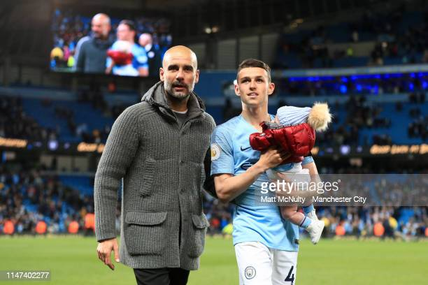 Josep Guardiola Manager of Manchester City celebrates victory with Phil Foden of Manchester City and his child during the Premier League match...