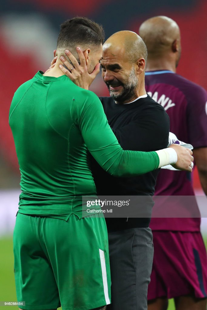Josep Guardiola, Manager of Manchester City celebrates victory with Ederson of Manchester City after the Premier League match between Tottenham Hotspur and Manchester City at Wembley Stadium on April 14, 2018 in London, England.