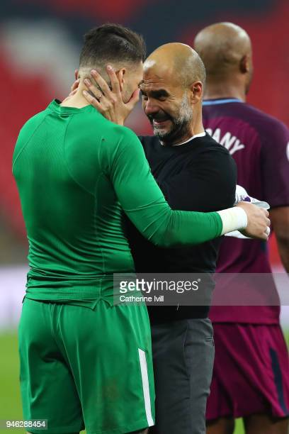 Josep Guardiola Manager of Manchester City celebrates victory with Ederson of Manchester City after the Premier League match between Tottenham...