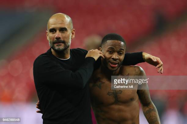 Josep Guardiola Manager of Manchester City celebrates victory with Raheem Sterling of Manchester City after the Premier League match between...