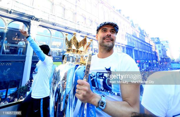Josep Guardiola Manager of Manchester City celebrates with the Premier League trophy on a parade bus during the Manchester City Teams Celebration...