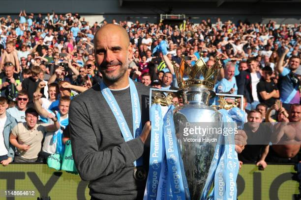 Josep Guardiola, Manager of Manchester City celebrates with the Premier League Trophy after winning the title following the Premier League match...