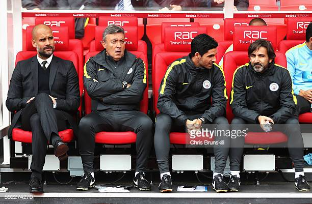 Josep Guardiola Manager of Manchester City Domenec Torrent Mikel Arteta and Lorenzo Buenaventura on the bench during the Premier League match between...