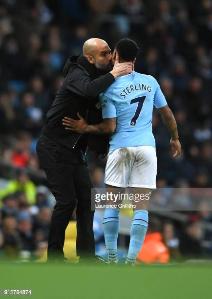 Josep Guardiola Manager of Manchester City embraces Raheem Sterling of Manchester City during the Premier League match between Manchester City and...