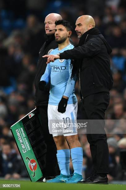 Josep Guardiola Manager of Manchester City in discussion with Sergio Aguero during the Carabao Cup SemiFinal First Leg match between Manchester City...