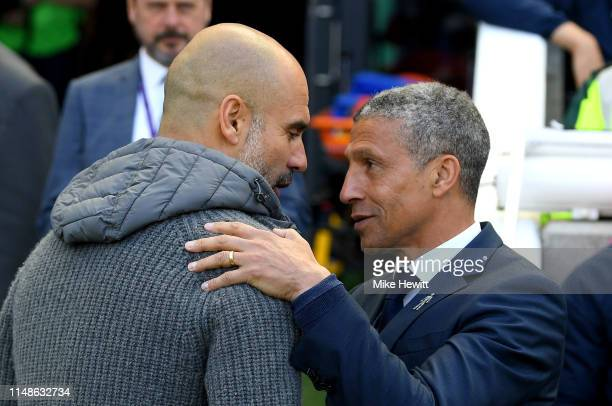 Josep Guardiola Manager of Manchester City is greeted by Chris Hughton Manager of Brighton and Hove Albion during the Premier League match between...