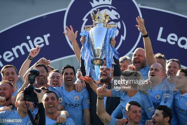 Josep Guardiola Manager of Manchester City lifts the trophy as Manchester City staff celebrate winning the Premier League title following the Premier...