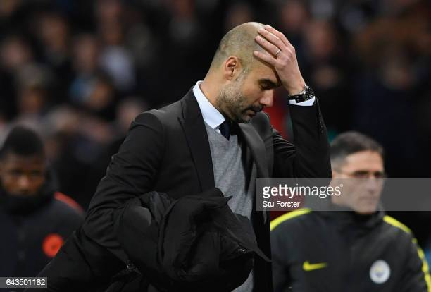 Josep Guardiola manager of Manchester City looks despondent at half time during the UEFA Champions League Round of 16 first leg match between...