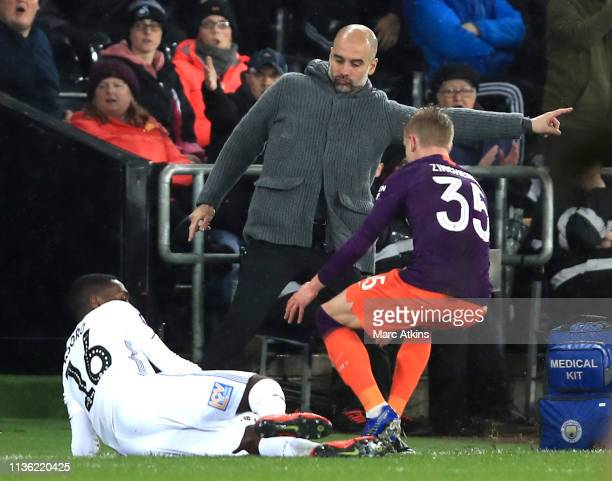 Josep Guardiola Manager of Manchester City looks on as Joel Asoro of Swansea City battles for possession with Oleksandr Zinchenko of Manchester City...