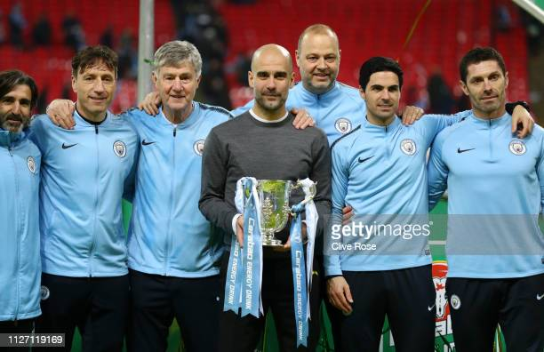 Josep Guardiola Manager of Manchester City poses for a photo with the trophy and his coaching staff following victory in the Carabao Cup Final...