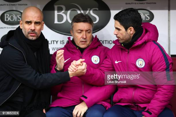 Josep Guardiola Manager of Manchester City shakes hands with Mikel Arteta during the Premier League match between Burnley and Manchester City at Turf...