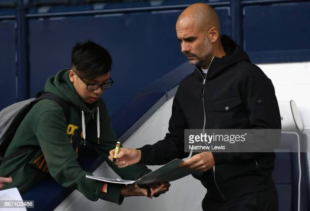 Josep Guardiola Manager of Manchester City signs autographs prior to the Premier League match between West Bromwich Albion and Manchester City at The...