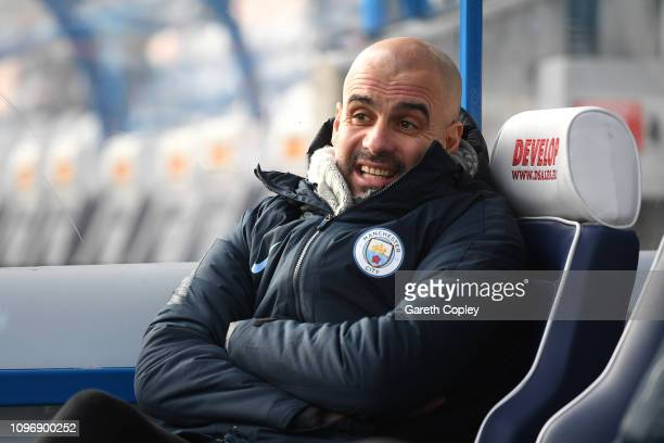 Josep Guardiola Manager of Manchester City sits on the bench ahead of the Premier League match between Huddersfield Town and Manchester City at John...