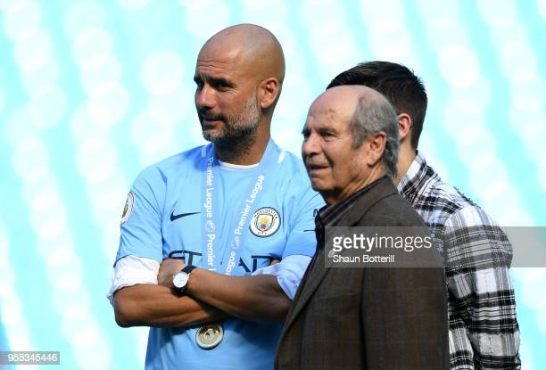Josep Guardiola, Manager of Manchester City speaks to his dad Valenti Guardiola on the pitch after the Premier League match between Manchester City...