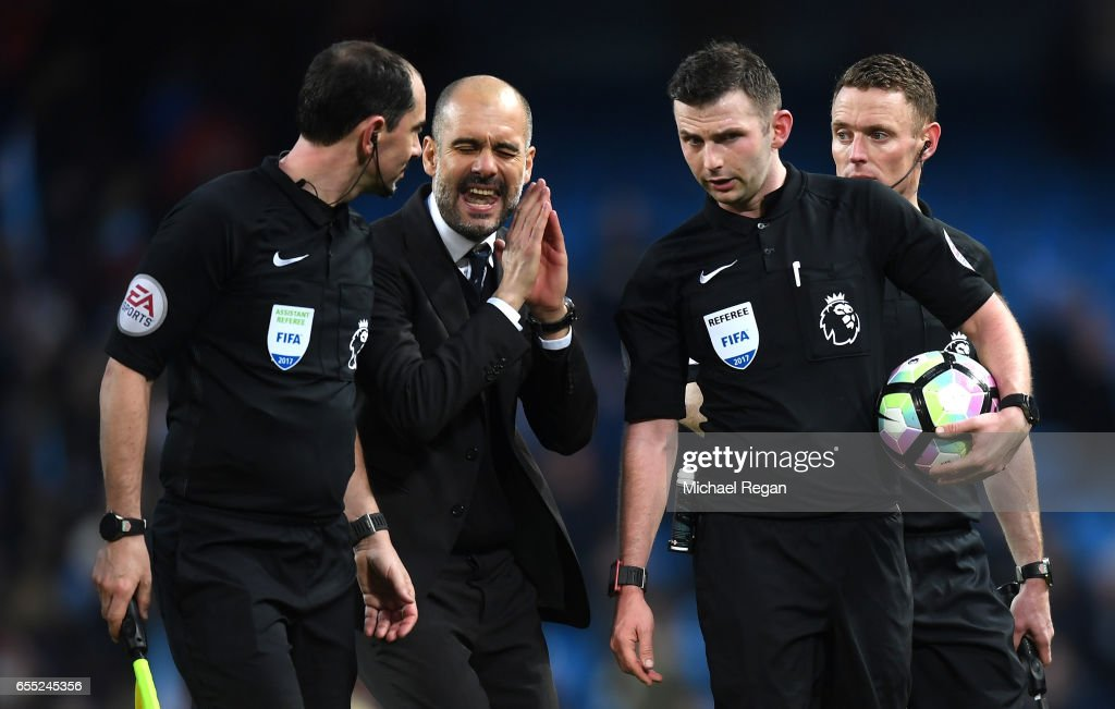Josep Guardiola, Manager of Manchester City (L) speaks to referee Michael Oliver after the Premier League match between Manchester City and Liverpool at Etihad Stadium on March 19, 2017 in Manchester, England.