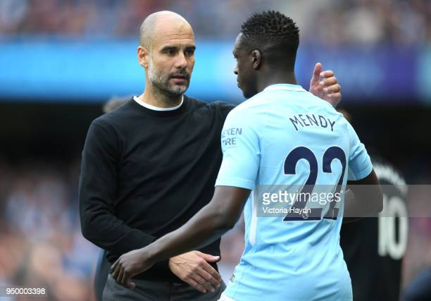 Josep Guardiola Manager of Manchester City speaks with Benjamin Mendy during the Premier League match between Manchester City and Swansea City at...