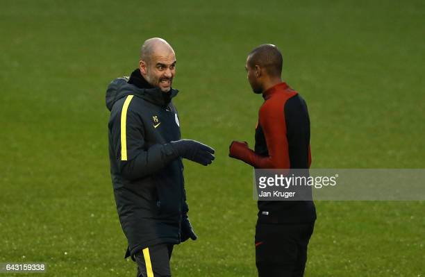 Josep Guardiola Manager of Manchester City speaks with Fernando of Manchester City during a Manchester City training session and press conference...