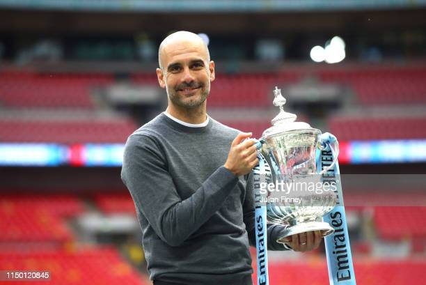 Josep Guardiola Manager of Manchester City stops for a photograph with the trophy following victory in the FA Cup Final match between Manchester City...
