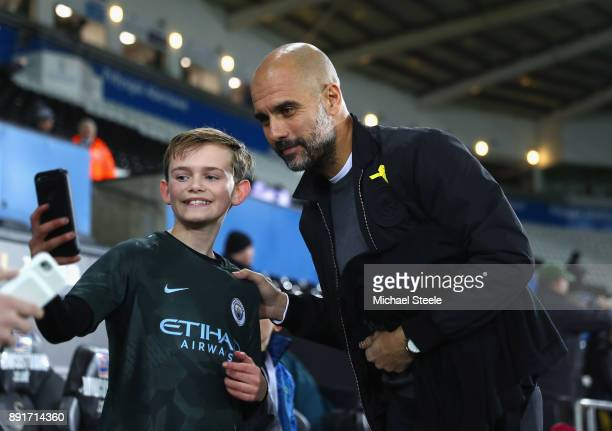 Josep Guardiola Manager of Manchester City takes a photo with a fan as he arrives prior to the Premier League match between Swansea City and...