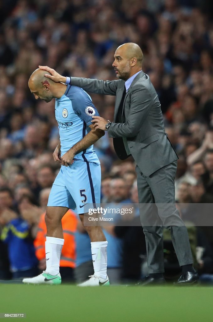 Josep Guardiola, Manager of Manchester City talks with Pablo Zabaleta of Manchester City as he goes onto the pitch as a second half substitute during his last home match for the club during the Premier League match between Manchester City and West Bromwich Albion at Etihad Stadium on May 16, 2017 in Manchester, England.
