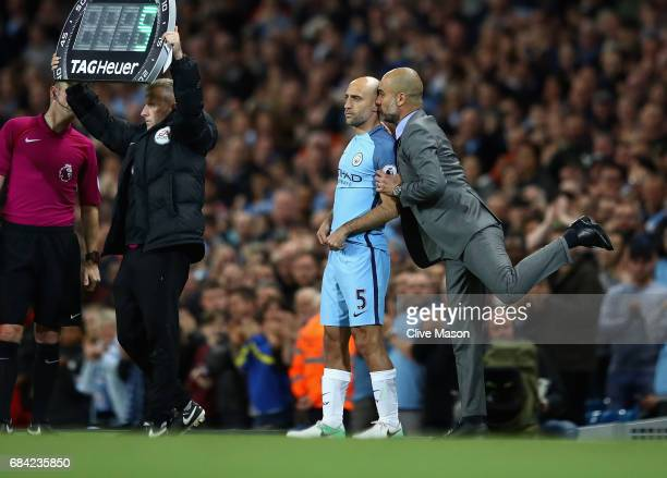 Josep Guardiola Manager of Manchester City talks with Pablo Zabaleta of Manchester City as he goes onto the pitch as a second half substitute during...
