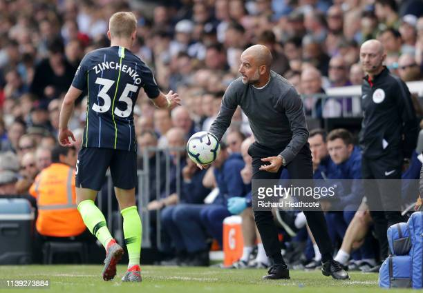 Josep Guardiola Manager of Manchester City throws the ball to Oleksandr Zinchenko of Manchester City during the Premier League match between Fulham...