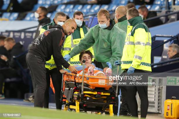 Josep Guardiola of Manchester City checks on Adrian Bernabe as he is being stretchered off during the Carabao Cup Third Round match between...
